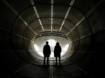 Two people standing in a cold war era bunker with their backs to the camera