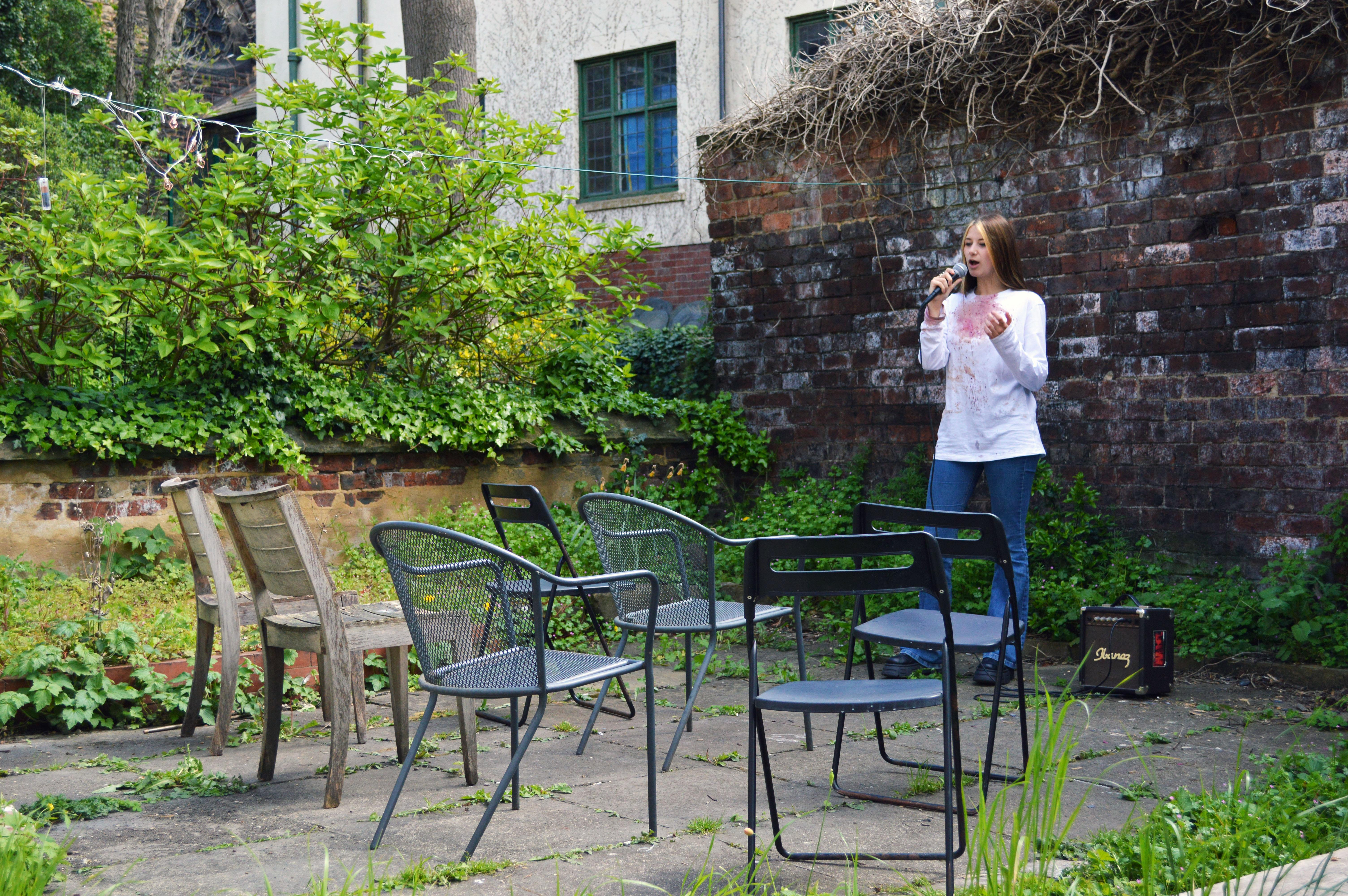 Artist  Olivia Russell performing to empty chairs in a garden during lockdown.