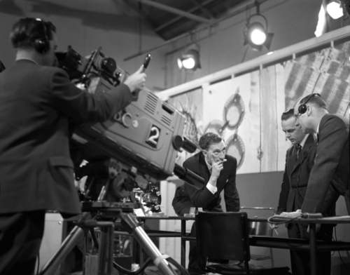 Black and white image of men in suits in a TV recording studio