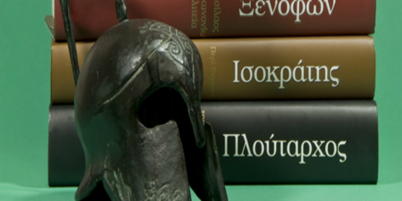 An image of a Greek-style helmet in front of Greek books with a green background.