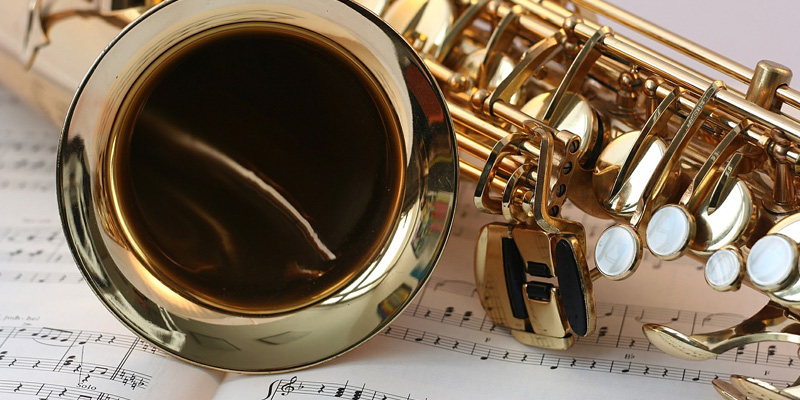 Saxophone lying on top of music sheets