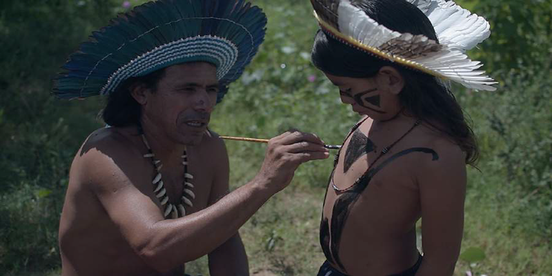 indigenous dressed man applying paint to child's chest
