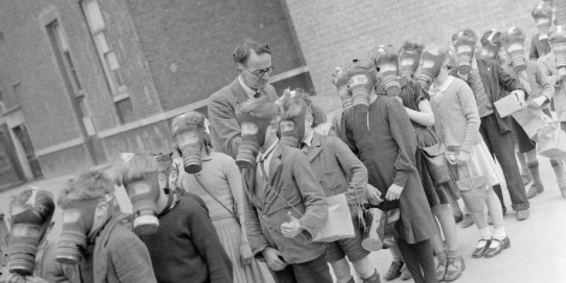 Image of school children wearing gas masks standing in a queue. A man, presumably their teacher, is looking over them.