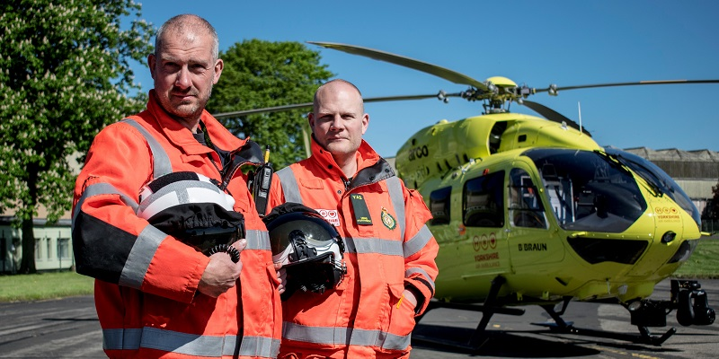 Two air ambulance workers next to helicopter