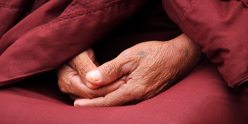 Hands folded in lap of Buddhist monk robes