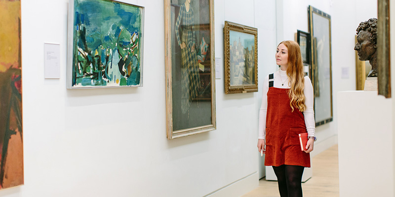 Student walking through a gallery with paintings hung on the walls.