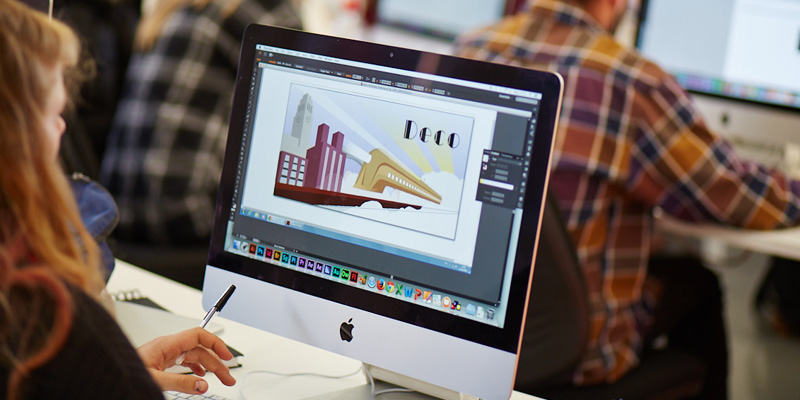 A student working on graphic design software on a desktop.