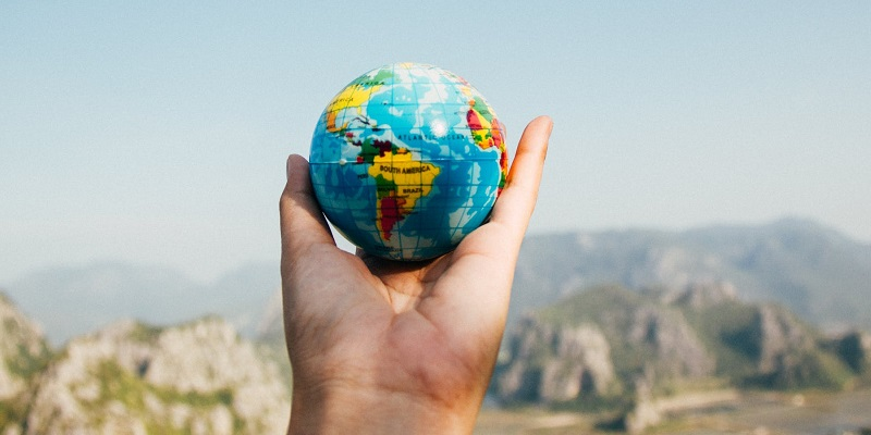 An outstretched hand holding a small globe, with mountains in the background