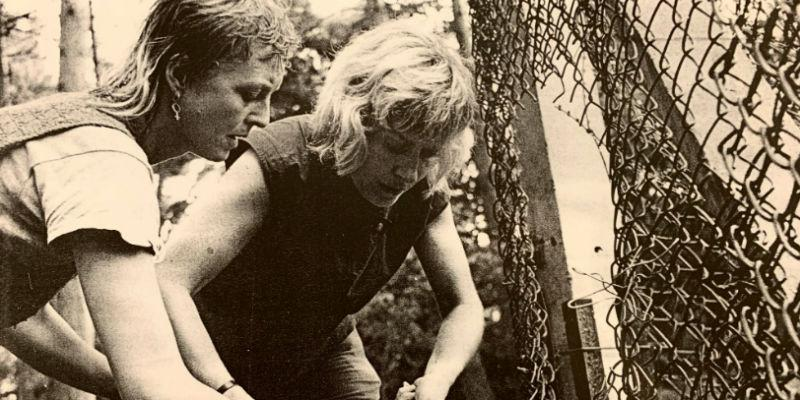 Two Greenham Common women cutting the wire of a fence. Image from the Feminist Archive North