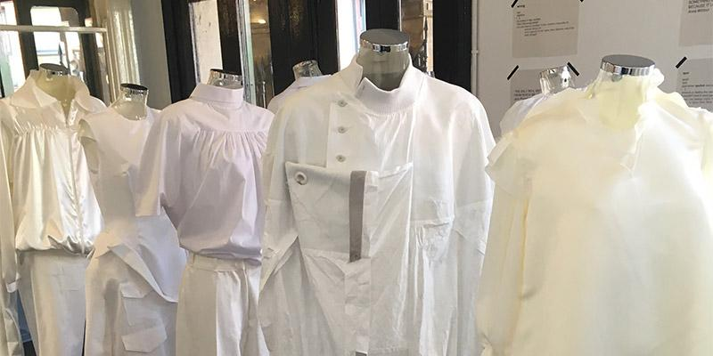 Line up of mannequins dressed in white clothing in various styles