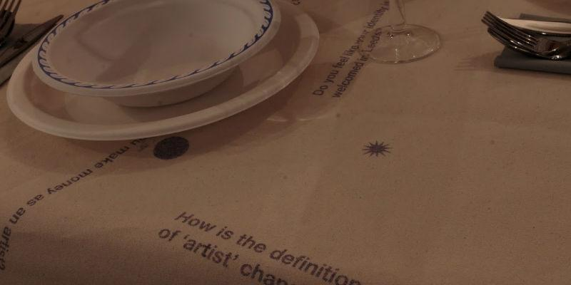 Installation by Nocturne of a table setting and screen printed statements about art and artists.