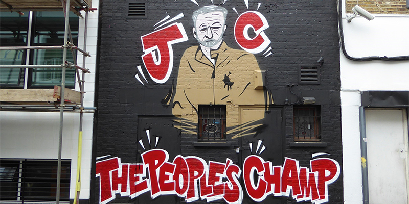 Graffiti picture of Jeremy Corbyn with the caption JC the people's champ