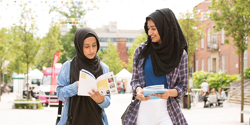 Two students walking together looking at a campus map outside.