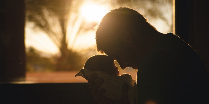 Close-up silhouette of a parent holding a baby with sunset behind.