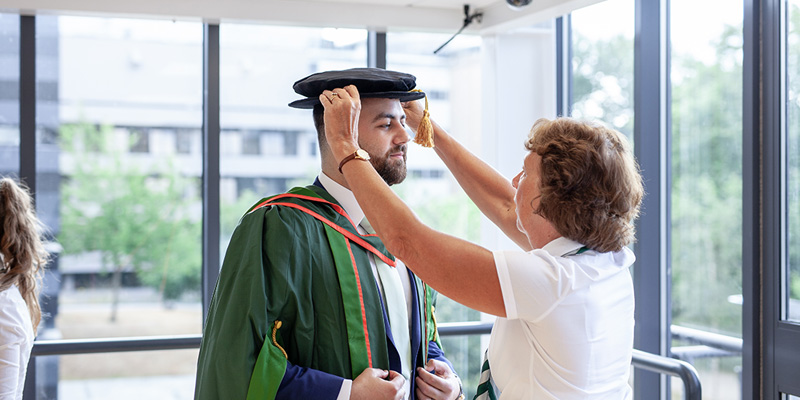 Student having gown fitted for graduation