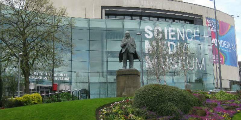 A photo of The National Science and Media Museum in Bradford, with a tree, lawn, plants and a statue in front of it.