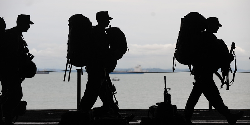 Silhouette of 3 soldiers marching with backpacks.