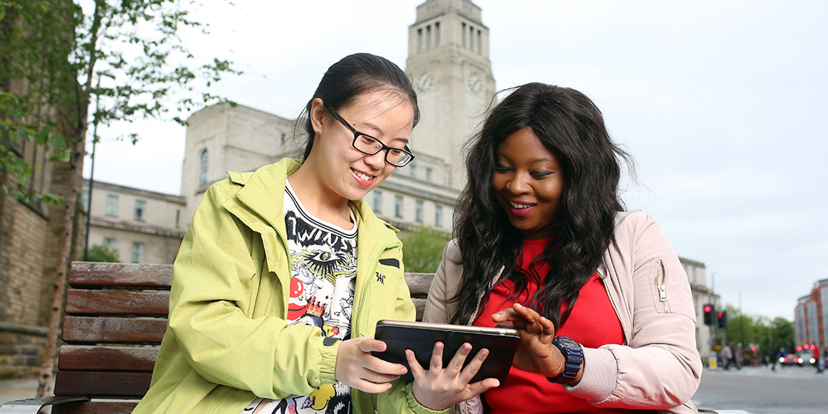 Two students sat on a bench reading from a tablet device