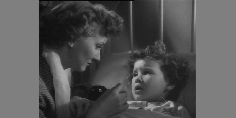 Woman looking at child in sick bed - still from film Emergency Call