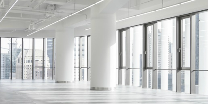 A photo of an empty office with a white floor, ceiling and columns, and floor to ceiling glass windows with high-rise buildings viewable from them.