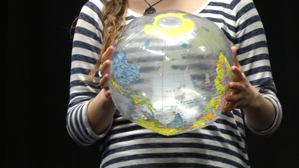 Female holding an inflatable globe in two hands