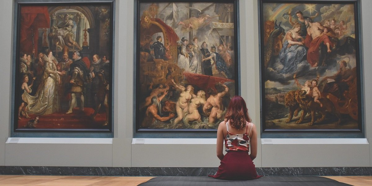 Seated woman looking at three large paintings in a gallery