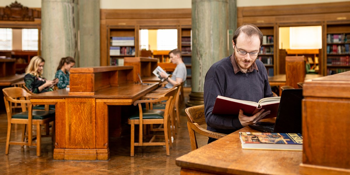Student in a library reading a book, other students in background working at desks
