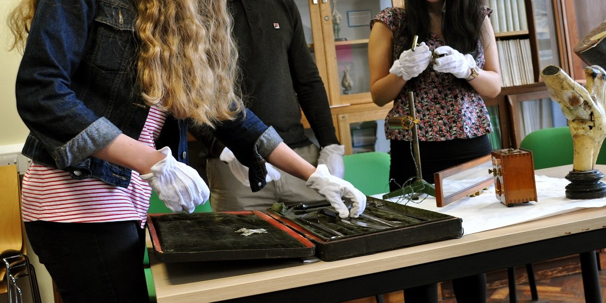 Students wearing protective gloves handling artefacts