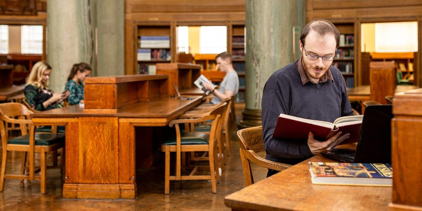 Image of postgraduate researcher reading a book in Brotherton Library