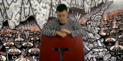 Film still from John Ledger's 'Wall, i' showing the lead character (played by Ben Crawford, in front of a painted wall.