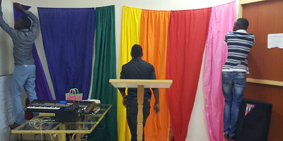 Kenyan's decorating a room with a rainbow flag