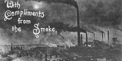Old black and white postcard of Widnes in the early 1900s, showing chimneys and dark smoke, with the words 'With Compliments from the Smoke'.