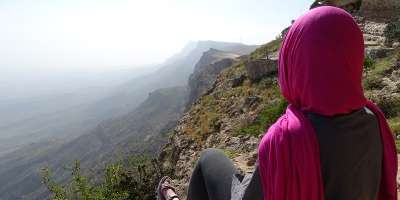 Prof Janet Watson in pink headscarf on a mountain in the middle east