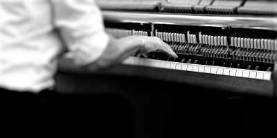 Male figure playing piano - black and white