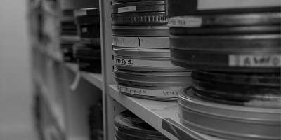 Image of film reels stacked high on shelves