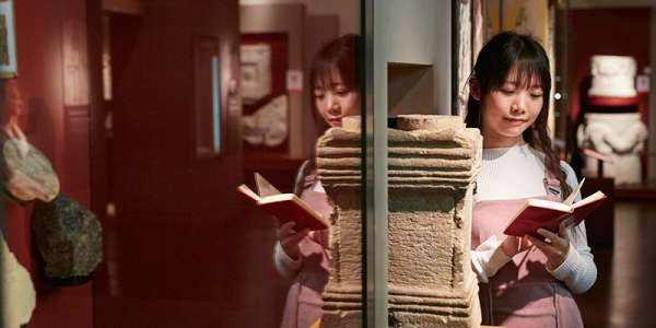 Student in museum reading book