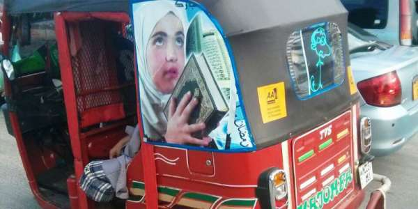 Motorized rickshaw with photo of a girl holding a holy book,