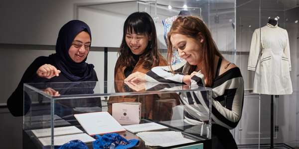 Three students looking at museum archives in glass cabinet