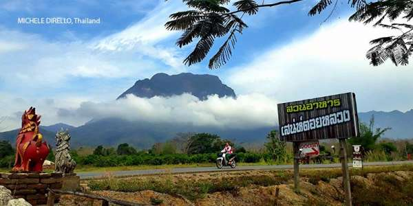 Cyclist in Thailand with mountains in the background