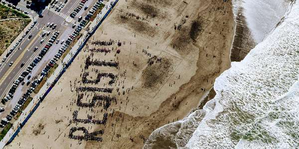 A birs-eye view of people spelling out the word 'resist!' on a beach, with waves lapping the shore.