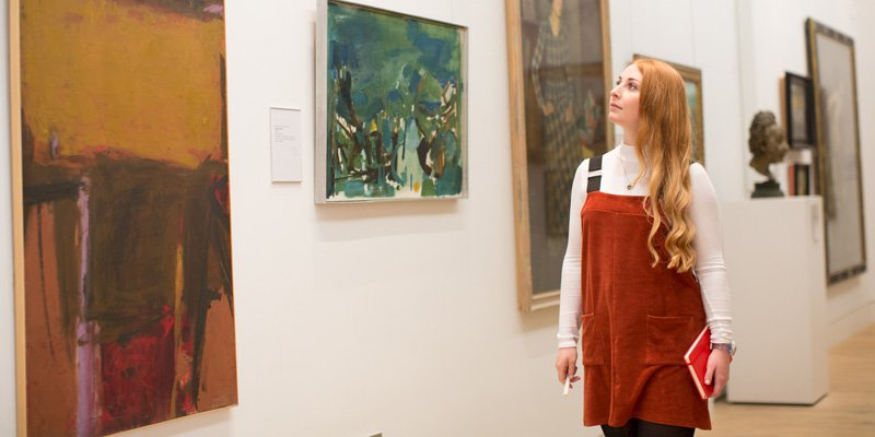 Student looking at artwork in gallery