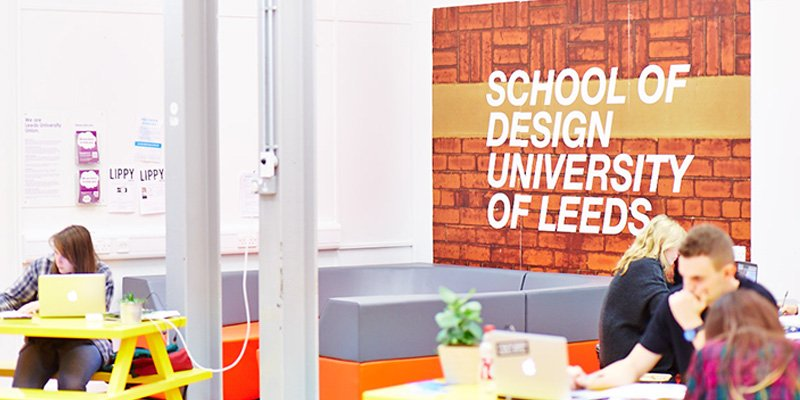 School of Design sign in the common room, surrounded by students working at picnic style tables.
