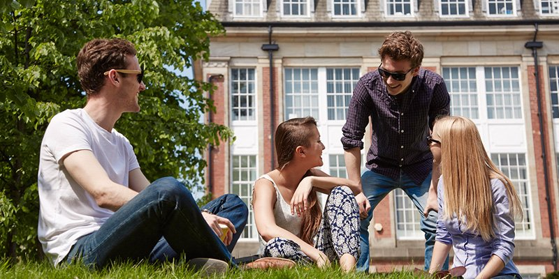 4 students sat on the grass outside the fine art building.